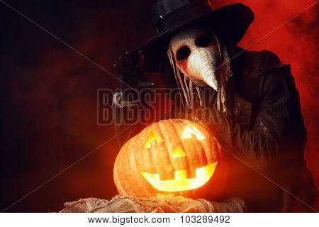 Frightening plague doctor stands with a pumpkin. Medieval Europe. Halloween.