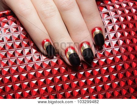 Beautiful women's manicure with black, red, gold polish on the nails