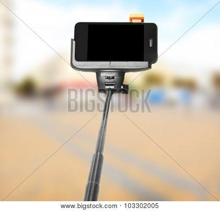 Selfie stick on city  background
