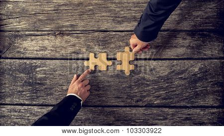 Retro Style Image Of Two Business Partners Each Placing One Matching Piece Of Puzzle On A Textured W