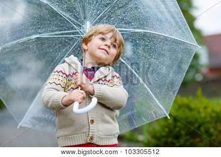Little Blond Kid Boy Walking With Big Umbrella Outdoors