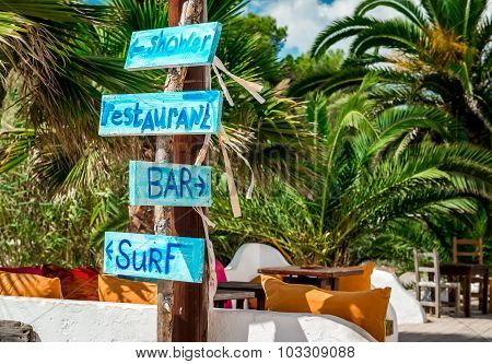Signboard with arrows. Shower bar restaurant and surf directions on the Ibiza nudist beach. Balearic islands Spain poster