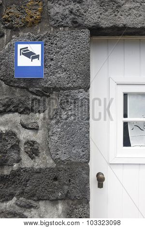 Rural Accomodation Signpost Over A Traditional Stone Facade, White Door