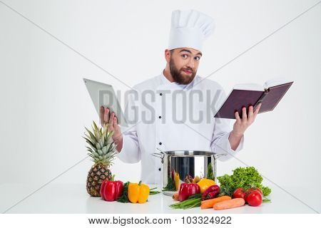 Portrait of a young male chef cook holding tablet computer and receipe book isolated on a white background