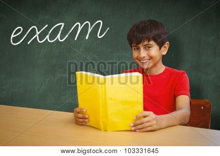 The word exam and portrait of boy reading book in library against green chalkboard