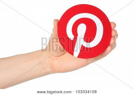 Hand holds Pinterest logotype printed on paper