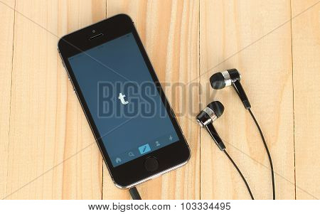iPhone with Tumblr logotype on its screen and headphones