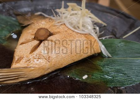 Hamachi cooked in sauce on black ceramic plate