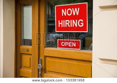 The Text Now Hiring Sticker Attached On Glass Door Of The Office poster