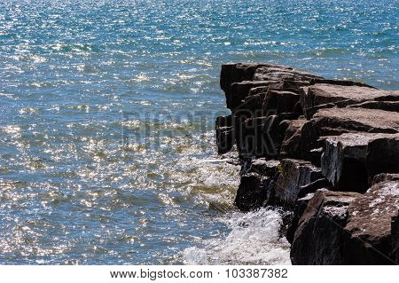 Waves On Sunny Day Splashing Against Breakwall