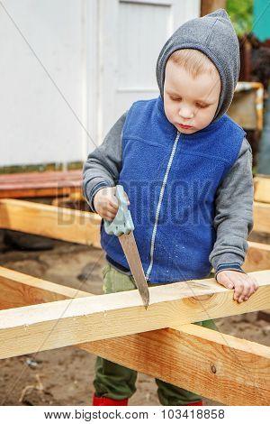 Little Studious Boy Sawing A Wooden Board. Home Construction. Little Helper.