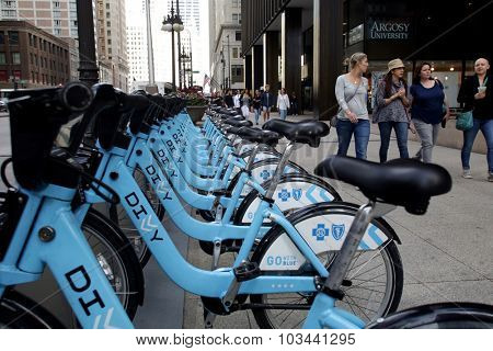 CHICAGO - FRIDAY, SEPTEMBER 25, 2015: Pedestrians walk past a Divvy bike rack. Divvy is a bicycle sharing system located in the City of Chicago.