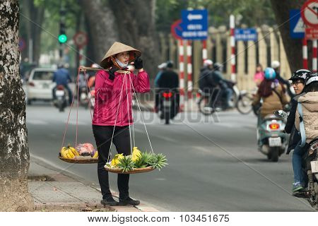HANOI, VIETNAM, DECEMBER 15, 2014 : A peddler carrying a traditional balance is selling bananas and pineapple in the streets of Hanoi, Vietnam