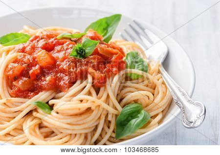 Spaghetti pasta with tomato sauce and basil herb garnish, simple ready to eat meal