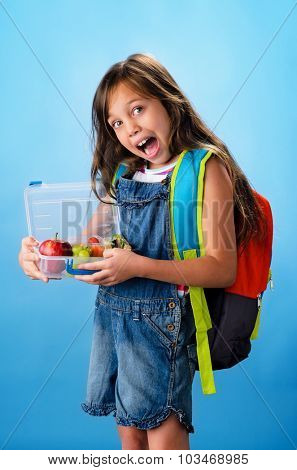 Happy smiling school girl holding healthy lunchbox filled with fresh fruit and sandwich on blue background