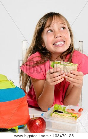 Happy smiling school girl looking up while holding healthy sandwich out of lunchbox filled with wholesome nutritious food