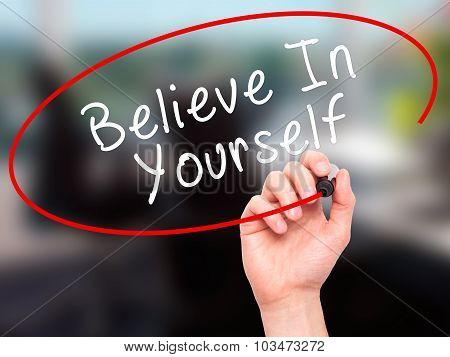 Man Hand writing Believe In Yourself with marker on transparent wipe board.