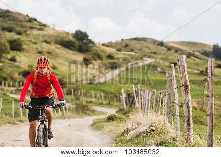 Mountain biker riding on bike in summer mountains landscape. Man cycling MTB enduro on rural country