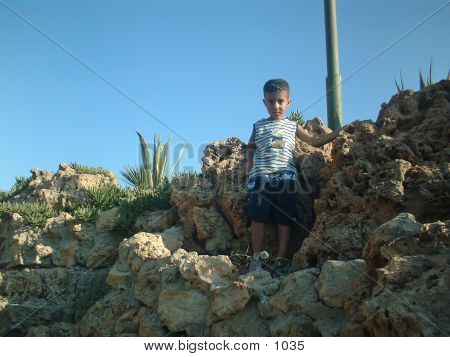 My son standing on a small cliff poster