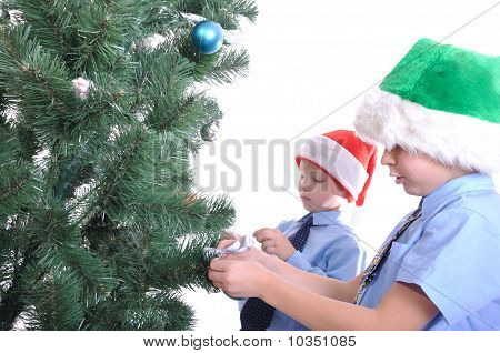 Boys Decorating A Christmas Tree