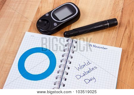 Glucometer, World Diabetes Day Written In Notebook And Blue Circle, Symbol Of Diabetic