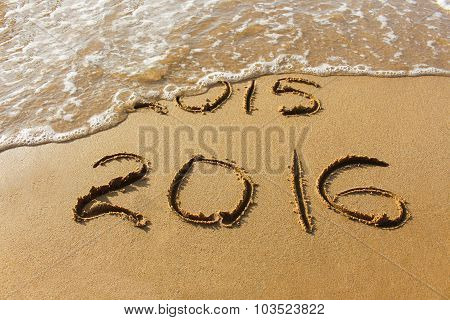 2015 and 2016 year written on sandy beach sea. Wave washes away 2015.