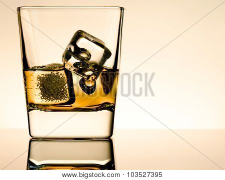 One Glass Of Whiskey With Ice Cubes On Table With Reflection, Light Brown Atmosphere
