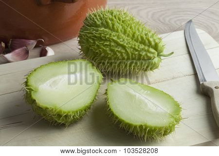 Whole and half spined fresh chayote fruit on a cutting board