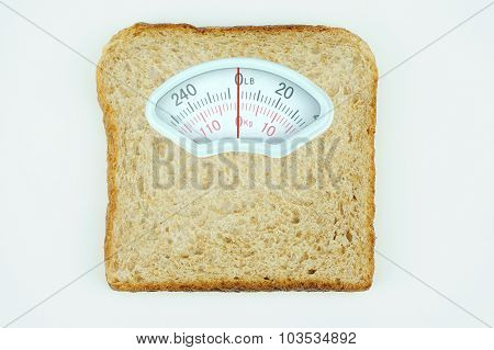 Weight scale with wholesome slice of bread on white background