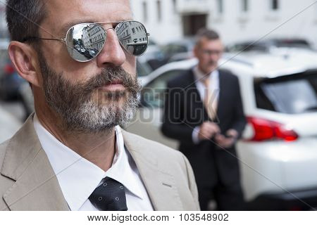 Closeup Of Man With glasses And Businessman In The Background