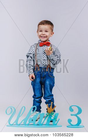 Laughing Boy In Blue Jeans With Braces On Grey Background