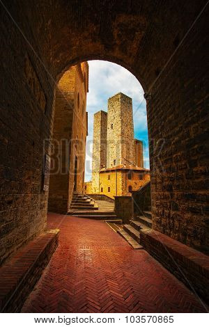San Gimignano Sunset From A Tunnel, Towers In Central Erbe Square. Tuscany, Italy, Europe.
