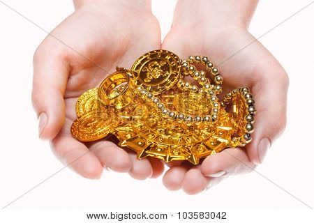 Handful of pirates coins in palm hands isolated on white