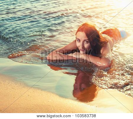 Young redhair teen girl lying at beach in sunset time and looking at you with her chin on her arms.