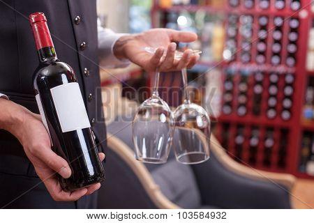 Skilled male sommelier is preparing wineglasses for drinking