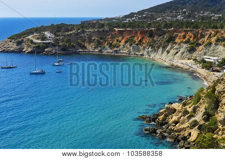 a panoramic view of the Cala de Hort cove in Ibiza Island, Spain, and its traditional fishermen shelters