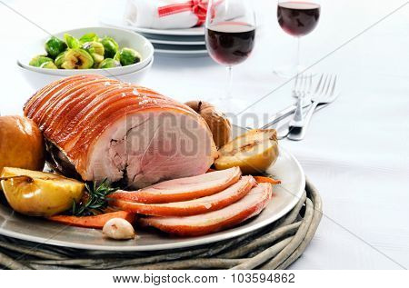Sliced pork roast served at a table set with vegetable sides, wine and cutlery
