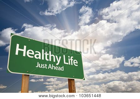 Healthy Life Green Road Sign With Dramatic Clouds and Sky.