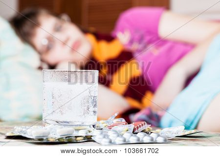 Glass With Dissolved Drug In Water And Pills