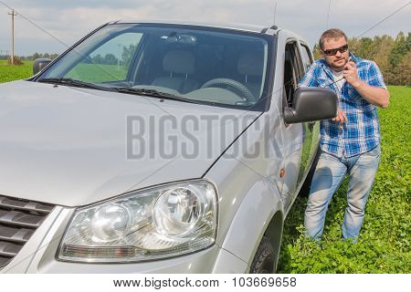 Man standing near car leaned on door and talking handheld transceiver
