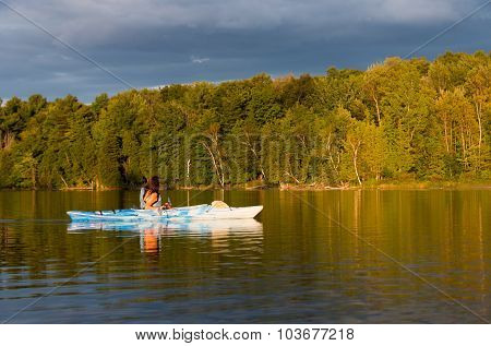 Woman Kayaking With Golden Light At Dusk