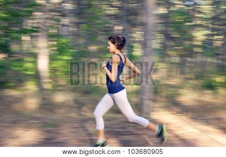 Young woman running on a rural road at sunset in autumn forest with motion blur effect. Lifestyle