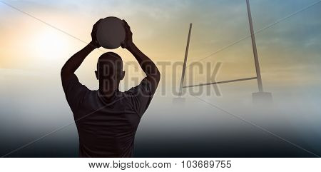 Rear view of athlete throwing rugby ball against goals posts