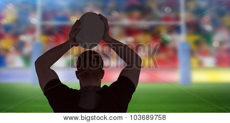 Rugby player about to throw a rugby ball against rugby stadium