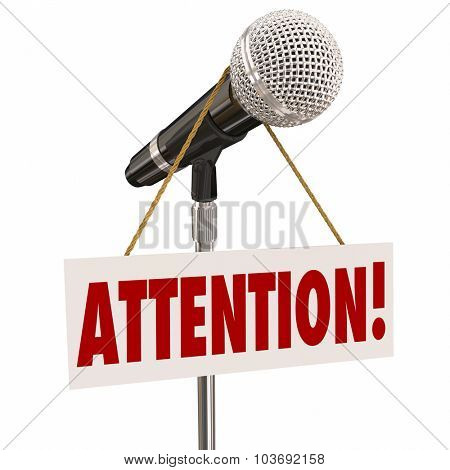 Attention word on a hnaging sign over a microphone urging you to listen or hear an important announcement, news or speech