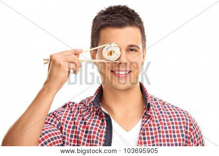 Young guy holding a piece of sushi with Chinese sticks in front of his right eye and looking at the camera isolated on white background