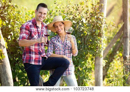 Cheerful couple of winegrowers drinking wine in vineyard