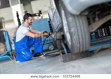 Car wheel change by mechanic with air wrench in workshop