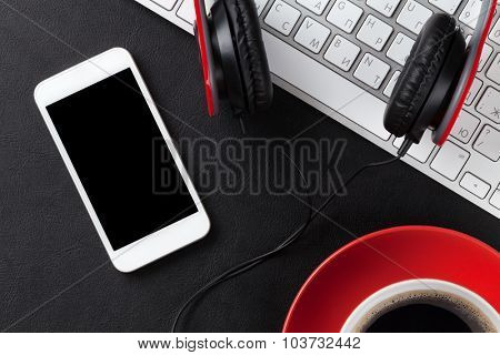 Office leather desk table with coffee cup, computer, smartphone and headphones. Top view poster