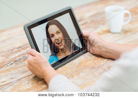technology, age, memories and people concept - happy senior woman with tablet pc computer viewing photo or having video chat with granddaughter at home